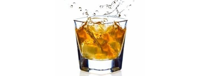 Ice cube splashing into a snifter of scotch.